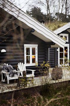 I det fredete villyngterrenget i Hornbæk i Danmark ligger en trygg og naturlig svartbeiset tømmerhytte - det perfekte landsted.