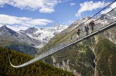 300 feet above an Alpine ravine, the Charles Kuonen Suspension Bridge forms part of the Europaweg — a two-day mountain trail which connects the towns of Grächen and Zermatt in Randa, Switzerland. Zermatt, Rando Velo, Places To Travel, Places To See, Pedestrian Bridge, Suspension Bridge, Destination Voyage, Swiss Alps, Wonders Of The World