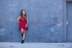 Senior girl pose against colorful blue brick wall. © Naccarato Photography, LLC. Portland, Oregon