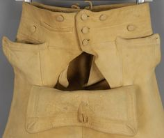Detail, breeches, Philadelphia, c. 1790. Deerskin, tan fall front with self buttons, single fob pocket and unusual side pockets having button flap extending over the side seam, double laced waist adjustment, four button leg closure with single hide tie.