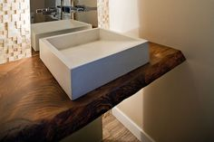 SYMMETRY + MATERIALITY  We designed and custom-fabricated the sink in white concrete to be monolithic modern but small-scaled to perfectly fit the space.  The wood top with the live edge is the perfect organic compliment to the crisp bold lines of the sink, faucet, and mirror.  In a mere three feet of wall space, we incorporated various tactile materials and drew upon the skills of multiple tradespeople and local artisans.