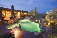 Custom free form pool with rock waterfall and reverse negative edge spa.