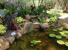 Charming backyard water garden in Richmond, TX features a constructed wetlands filter that adds an additional waterfall.