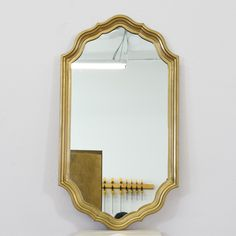 """This mirror is featured in a solid brass with a glossy metallic finish. This wall mirror is in great condition with intricate carved edges and curved trim. Regal mirror perfect for adding dimension to any space!  Dimensions: 21.75""""L x 2""""D x 39.75""""H   #regency #decor #mirror #sandiegovintage #vintagefurniture"""