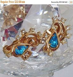 These #vintage aqua rhinestone earrings are absolutely beautiful!  They feature a gold plated setting with a large pear shaped aqua blue rhinestone surrounded by round clear... #ecochic #etsy #jewelry #jewellery