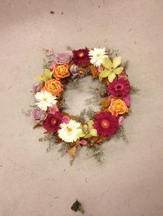 En krans med blader og roser, orkideer , Gerbra og lilla limonum