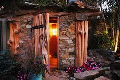 """The """"Earth House"""" sauna is constructed with stone, log timbers and a green roof, which hosts a combination of dwarf evergreens and ornamental grasses. The stone walls give the sauna a solid, grounded appearance and an artistic, craftsman quality. It was built by Outdoor Craftsmen, a Colorado company."""