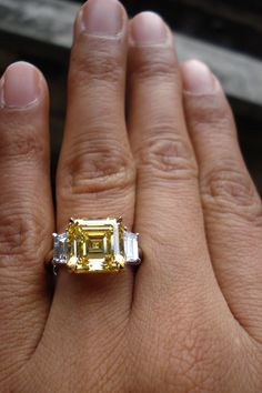 CENTER STONE:  WEIGHT: 6.01ct  SHAPE: Emerald Cut  COLOR: Fancy Vivid Yellow  CLARITY: VVS2  MEASUREMENTS: 10.08 x 9.99 x 6.54 mm  TOTAL DEPTH: 65.5%  TABLE SIZE: 63%  POLISH: VG  SYMMETRY: VG  FLUORESCENCE: NONE  GIA REPORT #: 17429567    SIDE STONES:  TOTAL WEIGHT: 1.02cts  QUANTITY: 2  SHAPE: Trapezoidal  COLOR: E-F  CLARITY: VS    MOUNTING:  Platinum and 18Karat Yellow Gold    Currently sized at: 6.5