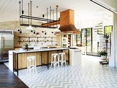 The open kitchen of Justin Hemmes's restored historic waterfront home is nothing short of stunning. The combination of Carrarra marble, copper hardware, and raw exposed brick in the...