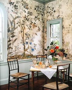 The appealing botanical wallpaper offset by solid lines- via solid waistcoat and window frames- are a perfect balance. Touches of orange from fresh flowers a delightful splash...Love this!
