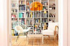 Biblioteca blanca empotrada, Acapulco turquesa con manta, sillón estilo escandinavo y tablones de madera anchos en el parquet