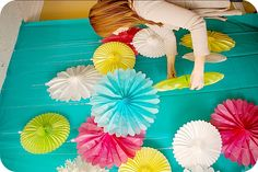 plastic table cloths + paper fans = fun photo booth backdrop