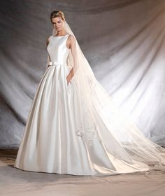 A tendência minimalista tem conquistado muitas noivas, e não é pra menos! Elegantíssimo vestido de noiva de micado com decote canoa e saia volumosa. Um belo corte princesa cheio de detalhes lindíssimos com fio bordado e pedraria nas costas. Um gracioso cinto realça a silhueta feminina.