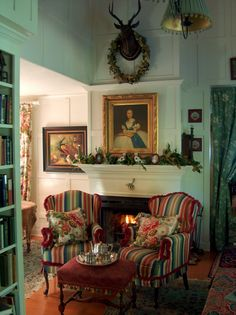 Brambly cottage - cosy chairs, fireplace and a little peep of a bookcase in the corner