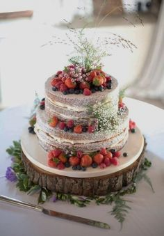 Two tiered naked cake with gypsophila, foliage and berries