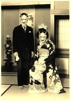 Couple with traditional Devil, or Oni-masks. Devil masks serve two purposes; the first, to portray the devil and create disasters or cause the plague, and conversely they are used to ward off evil spirits (As Fierce God Style). Used in Noh, Kabuki, and in celebration. Often handed down from generation to generation.