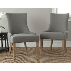 These gorgeous Lester dining chairs by Safavieh feature beautiful weathered oak legs and elegant gentle sloped arms with a slight hourglass shape. Upholstered in a modern granite gray linen, these chic chairs will lend posh style to your dining room.