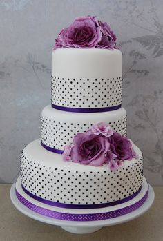 A purple sugar flower and black pok a dot modern wedding cake