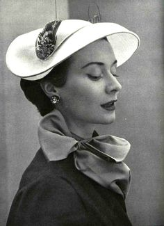 Model in broad hat trimmed in grey velour and feathers by Claude St. Cyr, photo Pottier, 1952