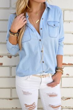 """We can't get enough of this chambray! With the soft feel, light blue shadeand subtle distressing, this will soon be your favorite top! Wear it with skinnies or tie it around your waist for the perfect casual look. Frayed hem and light distressing on left pocket.  100% Cotton 27"""" length 