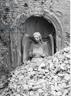 Stone figure of an angel half-buried in rubble following Allied bombing, Munich, 1945 (b/w photo)