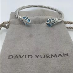 David Yurman Sterling Blue Topaz & Diamonds. David Yurman Sterling Blue Topaz & Diamonds Cable Wrap Bracelet   Price is negotiable just no low ball.  Hallmark:  © DY. 925  Size: 4mm  measurements: See photo above. Topaz Size: 10x10 mm  Diamond: .05cts  Pouch is Included David Yurman Jewelry Bracelets