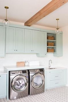 Laundry room with gray green cabinets paired with white quartz countertops and a white glass subway tiles backsplash.