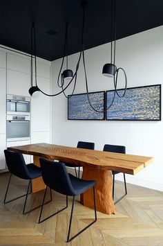 AIM by the Bouroullec brothers for completes this modern dining room arrangement featuring a long wooden table, bare walls with framed artwork and simple black chairs. Decor, Flos, Home Decor Items, Dining Inspiration, Interior Design, Parisian Apartment Decor, Interior Architecture, Modern Dining Room, Apartment Decor