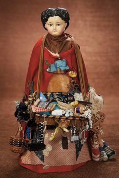 """14"""" (36 cm.) German Paper-mache shoulder head doll, ca. 1880.  The 14"""" doll is in original peddler attire with multi-layered costume,posed on original carved wooden pedestal,the doll carries a woven wicker tray that is laden with novelties,little dolls,sewing notions,buttons,and such."""