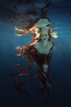 The girl in a red dress with ribbons under water