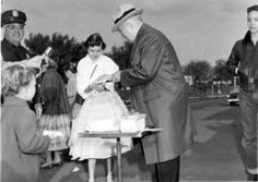Former President Harry S. Truman hands a piece of birthday cake to a young girl, as other unidentified children observe. Truman is at the train station, preparing to leave for a trip to Europe, May 8, 1956.