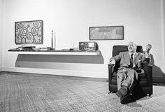 Mies van der Rohe delante de las paredes blancas de su casa, en el 200 de East Pearson Street, Chicago, en 1956. Las pinturas son de Paul Klee; la escultura, de Pablo Picasso; y el estante en voladizo, obra suya.