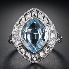 An unusually cut chubby marquise, or tapered oval (moval) aquamarine glistens from within a finely hand-crafted and richly detailed platinum mounting, circa 1920s-1930s