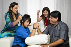 Boy and his father arm wrestling and their family cheering beside them Cheer, Arm, Father, Wrestling, India, Stock Photos, Couple Photos, Boys, Image