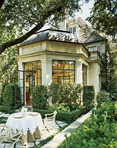 Ivory exterior with the contrast of the dark mullions on the windows, create a classic and elegant look. Love the patio setting with the moss filling in between the diagonal stones.