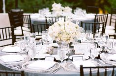 Grayish purple linens, silver trimmed flatware, white / blush centerpieces with mahogany chiavari chairs.