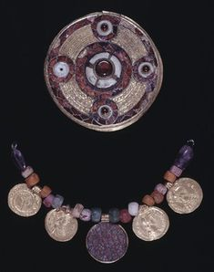 7th century, Early Anglo Saxon, Merovingian. (France but found in England) Gold composite disc brooch with 4 cabochon garnets in white paste & central boss; filigree; cloisonné; Style II pin-catch.  String of 16 glass and 2 amethyst beads (A), 4 gold coin pendants (B-E) and 1 millefiori pendant with gold rim (F).