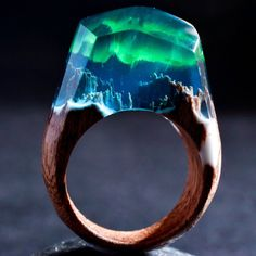 Aurora Borealis Magic in the skies to amaze the eyes. Bright northern lights bring endless delights. This ring is made of grey blue resin with green auroras. The base is sapele wood, a strong tree native to tropical Africa.