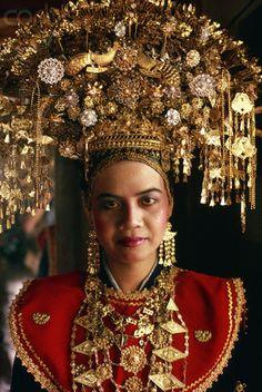 Sumatra, Indonesia | A Minangkabau bride wears an elaborate golden wedding headdress and golden jewelry. | © Owen Franken/Corbis