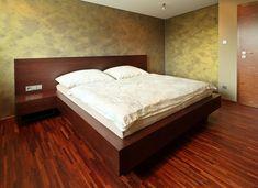 Krásná robustní postel z masivního dubu, která jasně vládne celé ložnici! Sytá barva mořeného dřeva skvěle ladí s tmavou podlahou a spolu s měchově zelenou malbou na stěnách přivádí celou místnost do zemitých přírodních tónů. Konstrukce postele je vysoká, ale relativně jednoduchá s širokým obdélníkovým čelem. Na to jsou nenápadně napojeny i noční stolky se šuplíky. Vypínače a zásuvky jsou pak integrovány přímo do čela pro rychlý a snadný přístup. Bed, Room, Furniture, Home Decor, Bedroom, Decoration Home, Stream Bed, Room Decor, Rooms