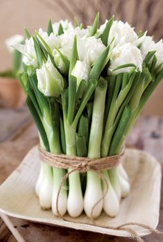 Rustic twine binds green onions and white flowers into a charming centerpiece.-- This is interesting