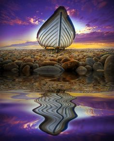'Scuse Me While I Kiss the Sky: Beautiful reflection in the water of a boat on the sea shore at sunset