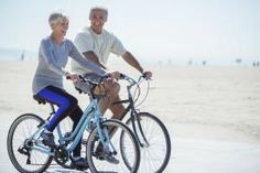 Photo of active older couple riding bicycles. - Paul Bradbury/Getty Images