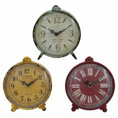 "Add a touch of vintage-inspired flair to your decor with this charming metal table clock, showcasing a rustic finish.   Product: Set of 3 table clocksConstruction Material: MetalColor: Rust red, yellow and tealDimensions: 7"" H x 6"" W x 2.5"" D each"