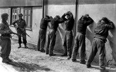 Foto-Aufnahmen Privat Ray Hurley von der US Army Signal Corps zeigt SS-Panzer-Besatzungen von Einheiten der 1. US-Infanteriedivision / 1. US-Armee gefangen genommen wurden, in Dorste (Deutschland) am 11. April 1945. Stehen halten sie ist Private First Class Herbert Lusk (rechts ) aus Demberton, West Virginia, und Sergeant Joseph F. Mannix kommen aus Tarent, Pennsylvania stamm