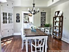 White cabinets, tan wall, wood floor, farmhouse table and blue mason jars....love it all!