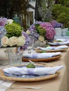 Gorgeous Hamptons garden party styling - with burlap table cloth, hydrangea and white rose centrepieces, and cane chargers to complete the look