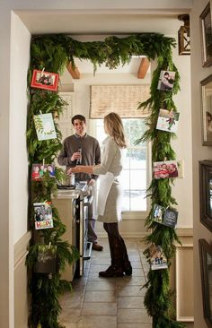 Christmas decorating idea: drape a doorway with fresh garland, then add clips to display holiday cards.