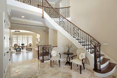 Foyer living room with wood stairs, wrought iron bannister, and elegant furniture Foyer Staircase, Curved Staircase, Staircase Design, Iron Staircase, Staircase Ideas, Grand Foyer, Grand Entrance, Entrance Halls, Entrance Foyer