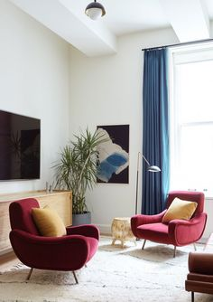 On the other end of the living room, a pair of Italian-modern chairs pay no mind to the nearby television; the hand-sculpted side table is from Collection20c, while the minimalistic media console is by Croft House.